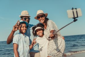 Smiling family taking a selfie on the beach