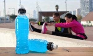 two sports drink bottles and two runners in the background stretching