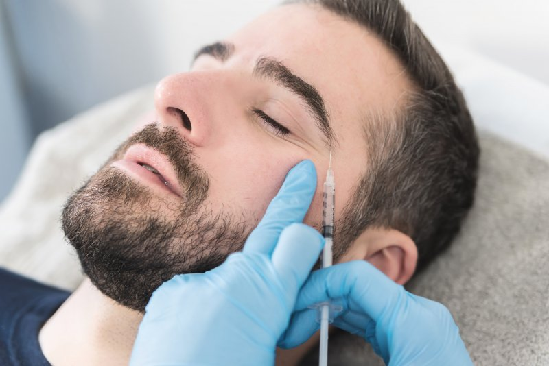a young man with a dark beard and his eyes closed receiving a BOTOX injection