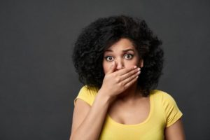 woman hides her cracked teeth during COVID-19
