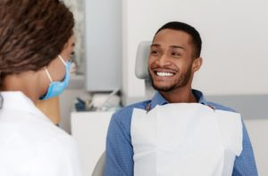 Dentist and patient discussing the difference between Invisalign and veneers